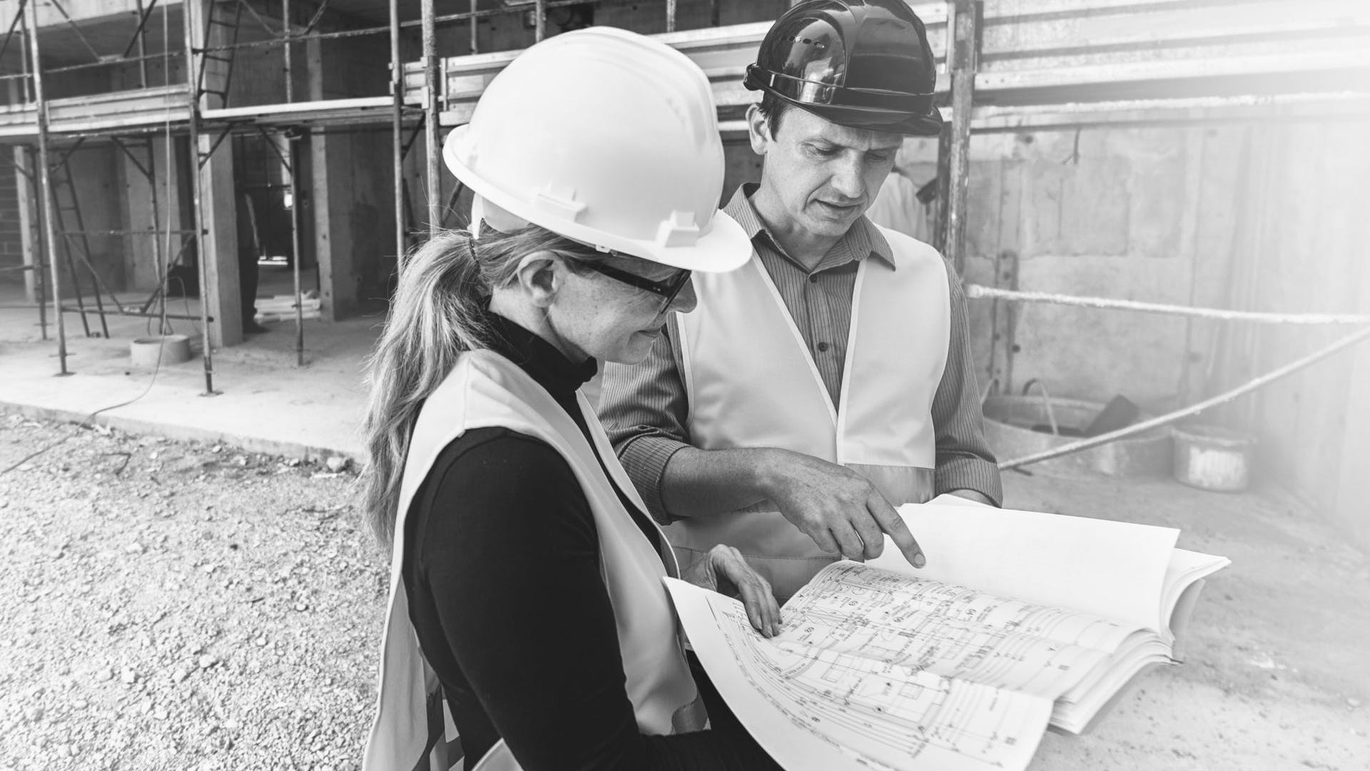 A man and a woman in a reflective clothing standing at a construction site and examining blueprints, scaffolding in background.